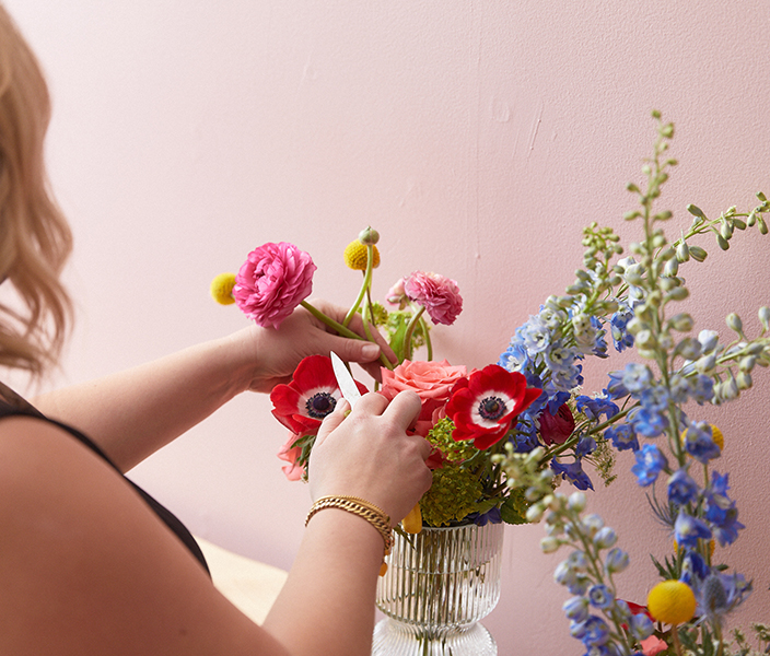 florist designing a vase arrangement