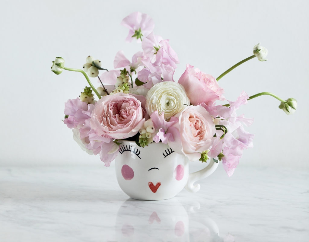 Smiley mug filled with sweet peas and garden roses